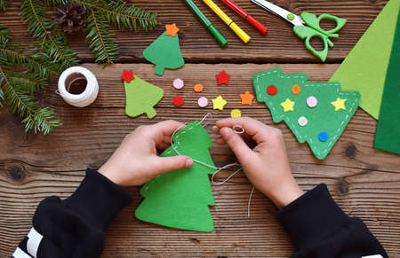 Photo pour Making of handmade christmas tree from felt with your own hands. Children's DIY concept. Making xmas toys decoration or greeting card - image libre de droit