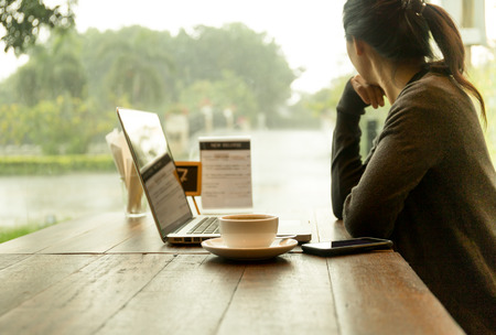 Foto de Asian woman with laptop with coffee on the table watching the rain out of window - Imagen libre de derechos