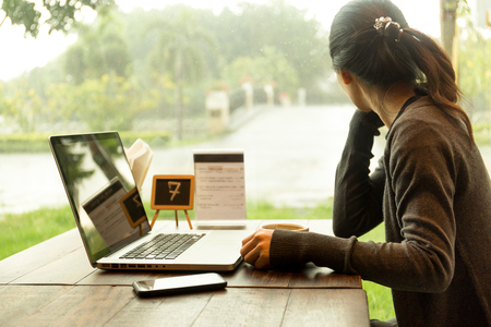 Photo pour Young casual woman with laptop and having coffee watching the rain out of window - image libre de droit