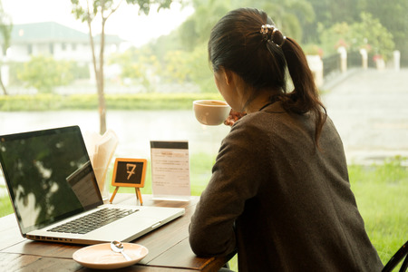 Photo pour Asian woman with laptop having coffee watching the rain out of window - image libre de droit