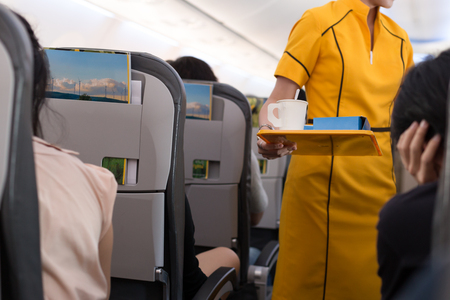 Foto de Flight attendant offering beverage to a passenger in flight jurney - Imagen libre de derechos