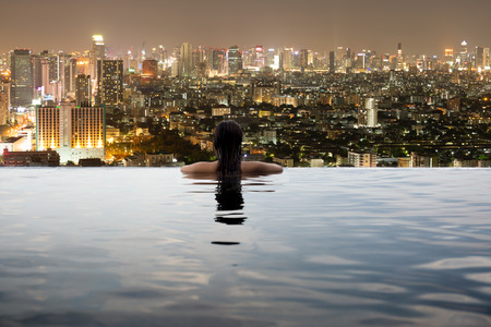 Photo pour Young woman in outdoor swimming pool with city view at night - image libre de droit