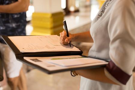Photo pour Receptionist filling in registration form at the hotel - image libre de droit