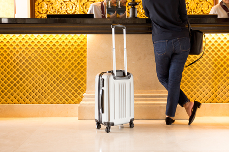 Photo for Woman tourist with suitcase chek in at reception hotel - Royalty Free Image