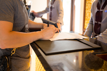 Photo pour Male guest check in at hotle signing a form at reception counter - image libre de droit