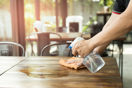 Photo pour Waiter cleaning the table with Disinfectant Spray in a restaurant - image libre de droit