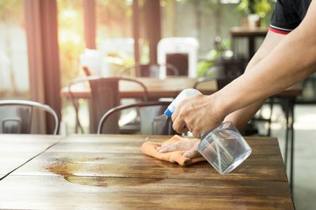 Foto de Waiter cleaning the table with Disinfectant Spray in a restaurant - Imagen libre de derechos