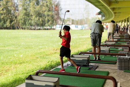Photo pour Young asian boy is practicing his golf swing at the golf driving range. - image libre de droit