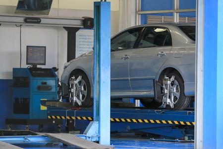 Photo pour suspension adjustment and automobile wheel alignment work at repair service station. - image libre de droit