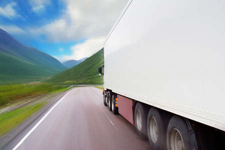 Motion of white semi-truck on the mountain road