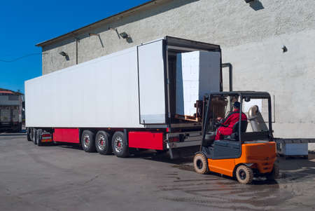 Photo for Worker on the loader unload white semi-trailer - Royalty Free Image