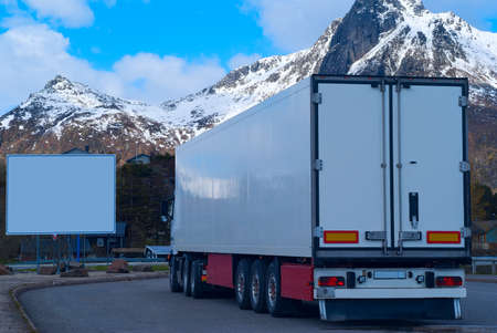 Foto de White refrigerated truck on background of the mountains and big white billboard - Imagen libre de derechos