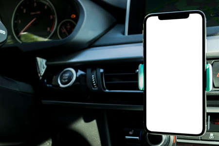 Foto de Smartphone in a car use for Navigate or GPS. Driving a car with Smartphone in holder. Mobile phone with isolated white screen. Blank empty screen. copy space. Empty space for text. modern car interior - Imagen libre de derechos