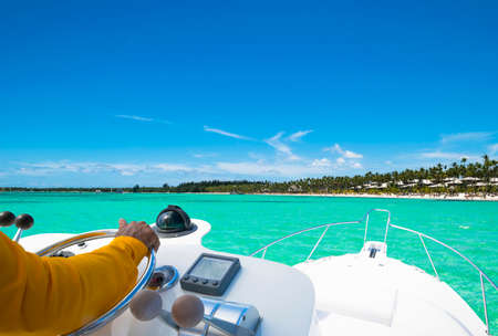 Photo pour Hand of captain on steering wheel of motor boat in the blue ocean during the fishery day. Success fishing concept. Ocean yacht - image libre de droit