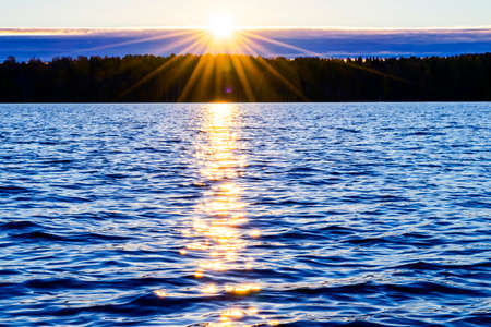 Foto de Water surface. View of a Sunset sky background. Dramatic gold sunset sky with evening sky clouds over the sea. View of a Crystal clear sea water texture. Landscape. Small waves. Water reflection - Imagen libre de derechos