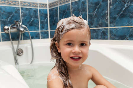 Photo for Cute little girl washes her hair. Clean kid after shower. Children hygiene. Child taking bath. Little baby in a kitchen sink washing hair with shampoo and soap. Water fun for kids. Hygiene and skin care for children. Bath room interior - Royalty Free Image