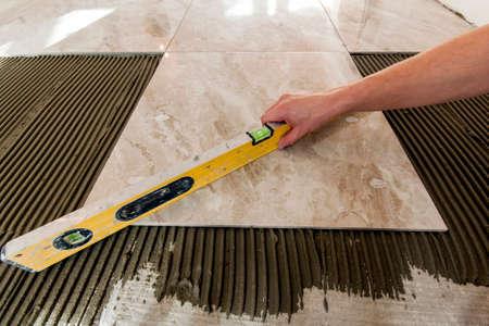 Photo pour Ceramic tiles and tools for tiler. Floor tiles installation. Home improvement, renovation - ceramic tile floor adhesive, mortar, level - image libre de droit
