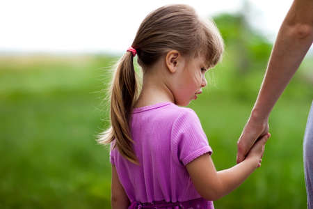Photo for Little girl holding a hand of her mother. Family relations concept. - Royalty Free Image