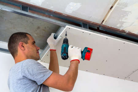 Photo pour Construction worker assemble a suspended ceiling with drywall and  fixing the drywall to the ceiling metal frame with screwdriver. - image libre de droit