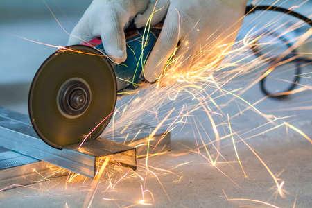 Foto de Close-up of worker cutting metal with grinder. Sparks while grinding iron. - Imagen libre de derechos