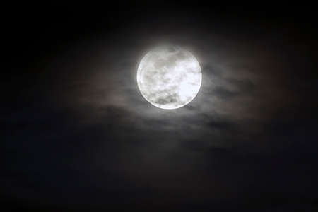 Photo pour Big silver glowing Moon close-up on dark blue sky with scattered clouds. - image libre de droit