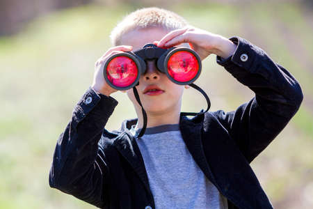 Photo for Portrait of little cute handsome cute blond boy watching intently something through binoculars in distance on blurred background. Children innocence, dreams, fantasies and imaginations concept. - Royalty Free Image