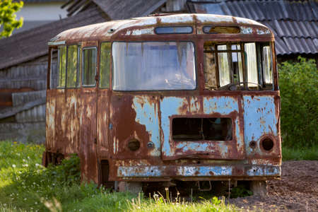 Photo for Close-up of old forsaken passenger bus with broken windows rusting in high green weedy grass on edge of plowed brown field on bright spring day under blue morning sky. - Royalty Free Image