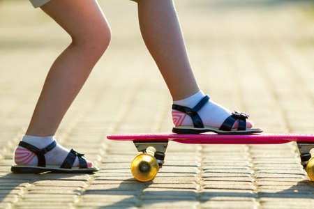 Photo pour Child slim legs in white socks and black sandals on plastic pink skateboard on bright sunny summer blurred copy space pavement background. Outdoors activities and healthy lifestyle concept. - image libre de droit
