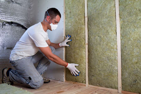 Photo pour Worker in protective goggles and respirator insulating rock wool insulation in wooden frame for future house walls for cold barrier. Comfortable warm home, economy, construction and renovation concept - image libre de droit