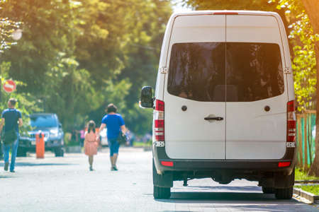 Photo pour Back view of white passenger medium size commercial luxury minibus van parked n shadow of green tree on summer city street i with blurred silhouettes of pedestrians and cars under green trees. - image libre de droit