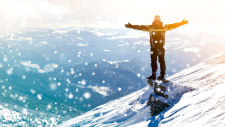 Foto de Silhouette of alone tourist standing on snowy mountain top in winner pose with raised hands enjoying view and achievement on bright sunny winter day. Adventure, outdoors activities, healthy lifestyle. - Imagen libre de derechos