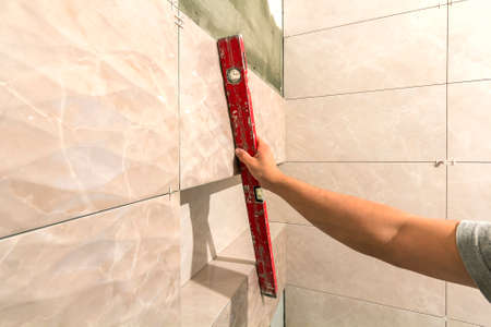 Foto de Close-up of worker tiler hand with lever installing on walls ceramic tiles. Tiles installation, tools and home improvement, renovation and construction, comfortable modern home concept. - Imagen libre de derechos