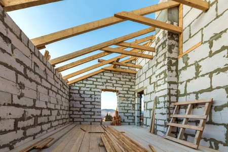 Photo for House interior under construction and renovation. Energy saving walls of hollow foam insulation blocks and bricks, ceiling beams and roof frame. - Royalty Free Image