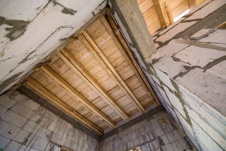 Photo for Close-up detail of house room interior under construction and renovation. Energy saving walls of hollow foam insulation blocks, wooden ceiling beams for roof frame. - Royalty Free Image