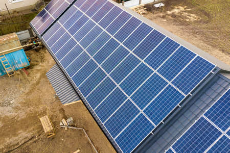 Photo pour Aerial top view of new modern residential house cottage with blue shiny solar photo voltaic panels system on roof. Renewable ecological green energy production concept. - image libre de droit