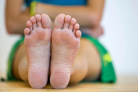 Photo pour Close-up of woman sitting on the floor with bare feet. Legs care and skin treatment concept. - image libre de droit