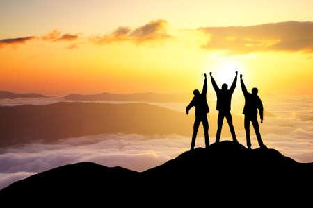 Photo pour Silhouettes of team on mountain peak. Sport and active life concept - image libre de droit