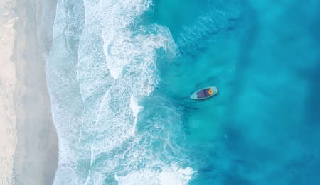 Foto de Wave and boat on the beach as a background. Beautiful natural background at the summer time from air - Imagen libre de derechos