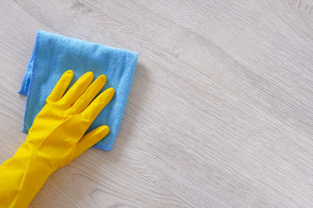 Photo pour Commercial cleaning company concept. Hand in rubber protective glove with blue microfiber cloth is wiping floor. Copy space. - image libre de droit