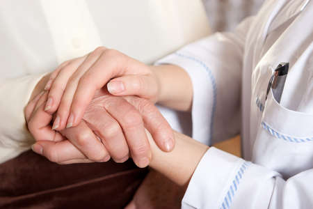 Foto de Helping hands: the nurse holds hands of the elderly female - Imagen libre de derechos