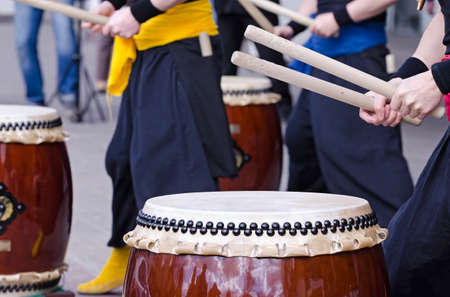 Photo for Group of japanese musicians are playing on traditional japanese percussion instrument Taiko or Wadaiko drums. The drumsticks are in the hands. - Royalty Free Image