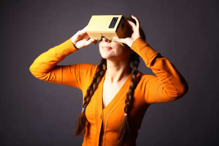 Foto de Color shot of a young woman looking through a cardboard, a device with which one can experience virtual reality on a mobile phone. - Imagen libre de derechos