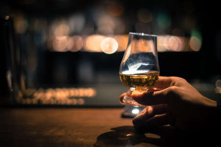 Photo for Close up shot of a hand holding a Glencairn single malt whisky glass. - Royalty Free Image