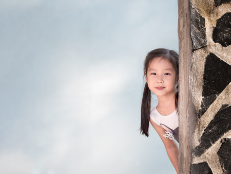 Photo for Asian girl hiding behind the wall, peekaboo action - Royalty Free Image