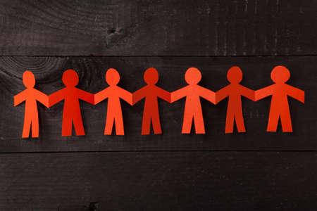 Foto de Group of paper doll holding hands. Teamwork concept papercraft. Orange dolls on black wooden background - Imagen libre de derechos