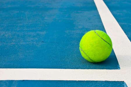 Green tennis ball on blue court