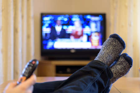 Foto de TV, television watching (news) with feet on the table and remote in hand - stock photo - Imagen libre de derechos