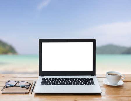 Foto de laptop computer and coffee on wood workspace and the beach background - Imagen libre de derechos