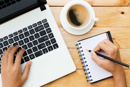 Photo pour hand using laptop and write note inspire idea on wood desk - image libre de droit