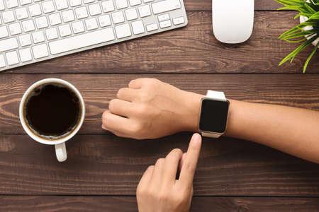 Photo pour hand using smartwatch on desk top view - image libre de droit